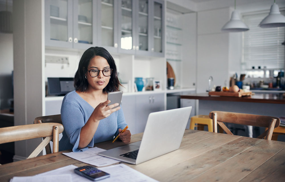 Woman sitting at kitchen table with computer and phone