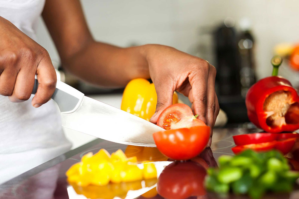 A person uses a knife to prepare fresh vegetables in a kitchen.