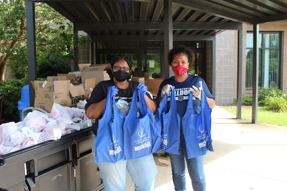 two women holding bags of supplies at united way event